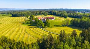 Panorama mit gemähten Wiesen und Bauernhof