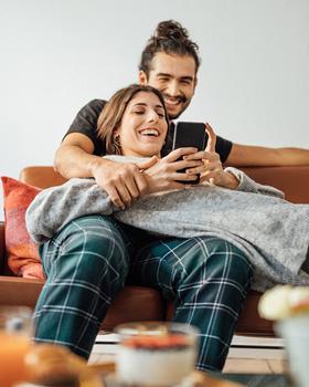 Frau und Mann liegen auf Sofa und schauen ins Smartphone