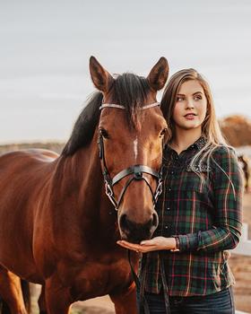 Frau steht neben Pferd und lässt Pferd an Hand schnuppern