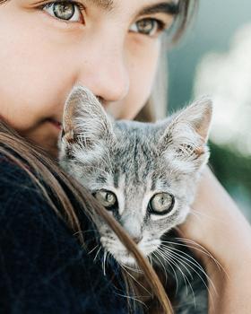 Mädchen kuschelt mit Katze
