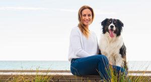 Frau sitzt neben Hund, Meer im Hintergrund