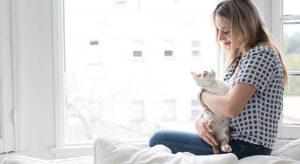 Frau sitzt vor Fenster mit Katze im Arm