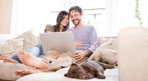 Frau und Mann sitzen auf Sofa mit Notebook