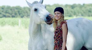 Mädchen mit Mütze legt Hand auf Nase eines Pferdes