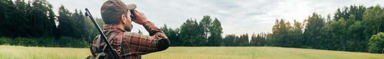 Jäger schaut mit Fernglas übers Feld in den Wald