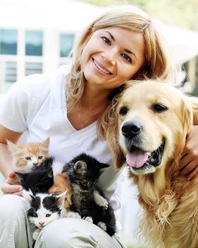 Frau mit Katzenjungen auf dem Schoss schmiegt sich an Hund