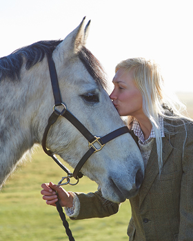 Frau küsst Pferd auf den Kopf