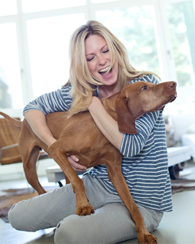 Frau hält Hund im Arm