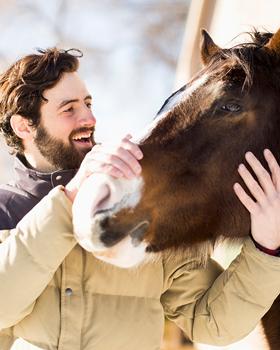Mann hält Pferdekopf