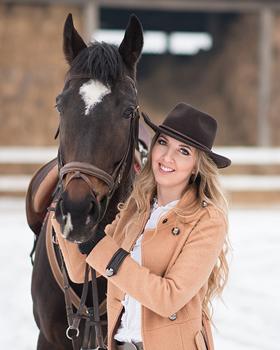Reiterin mit Westernhut steht neben Pferd