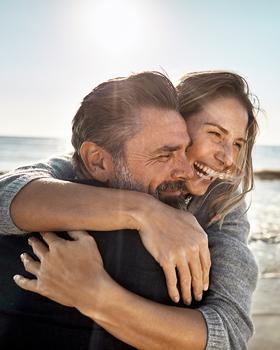 Mann und Frau umarmen sich am Stand