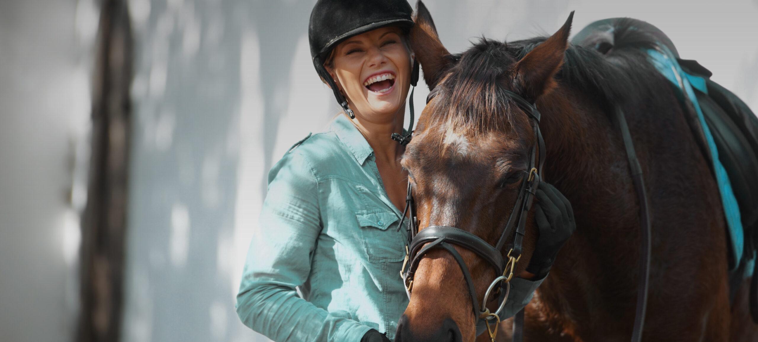 Reiterin mit Helm steht bei Pferd