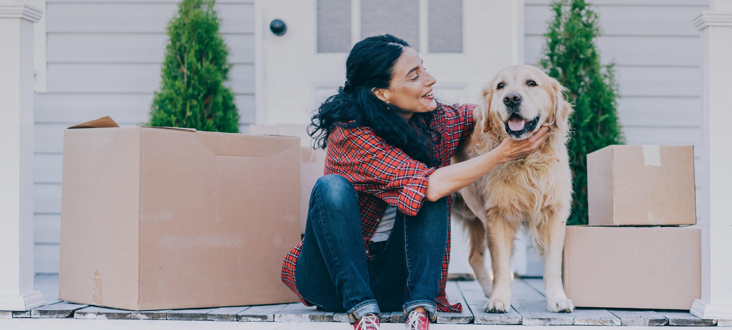 Frau sitzt mit Hund vor Haus umgeben von Kartons