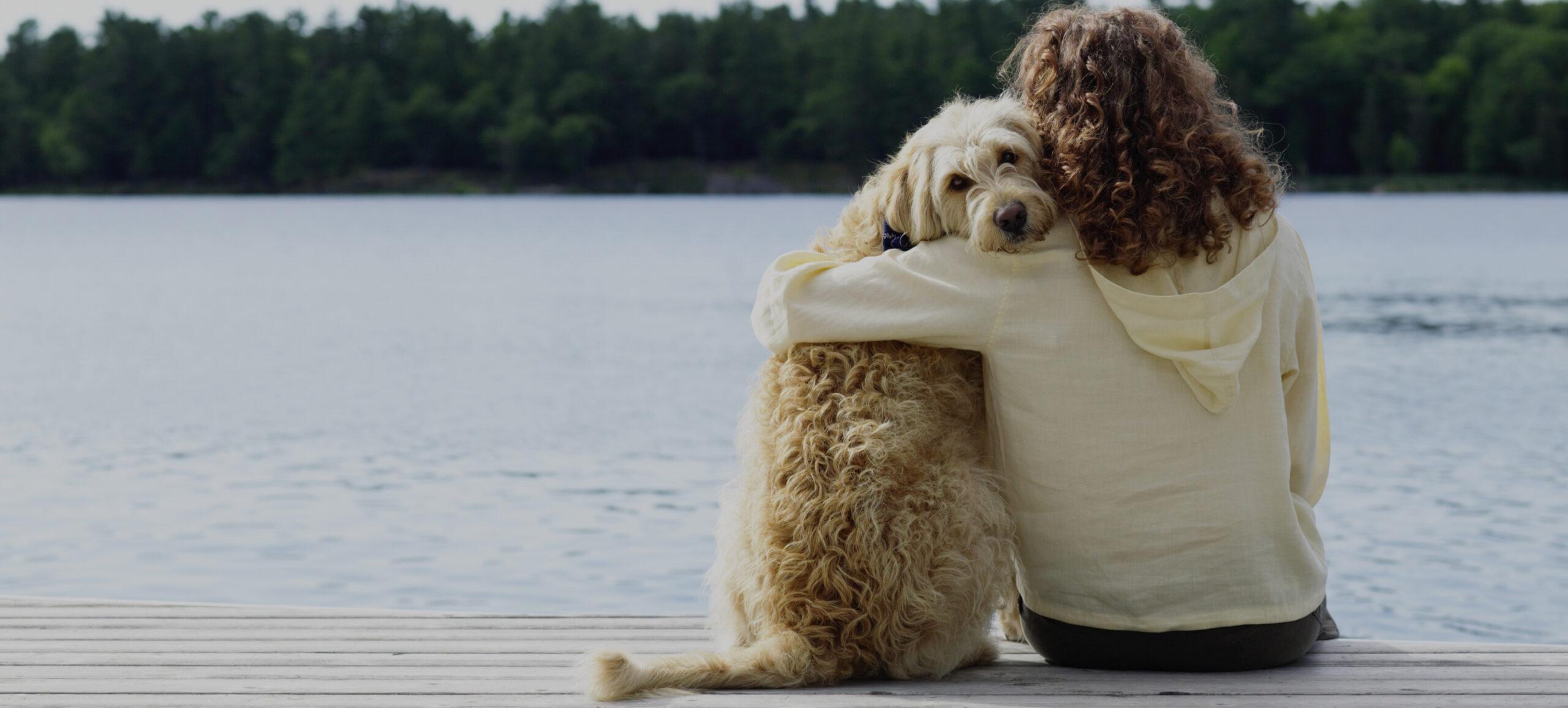Frau sitzt mit Hund auf Steg an Wasserkante