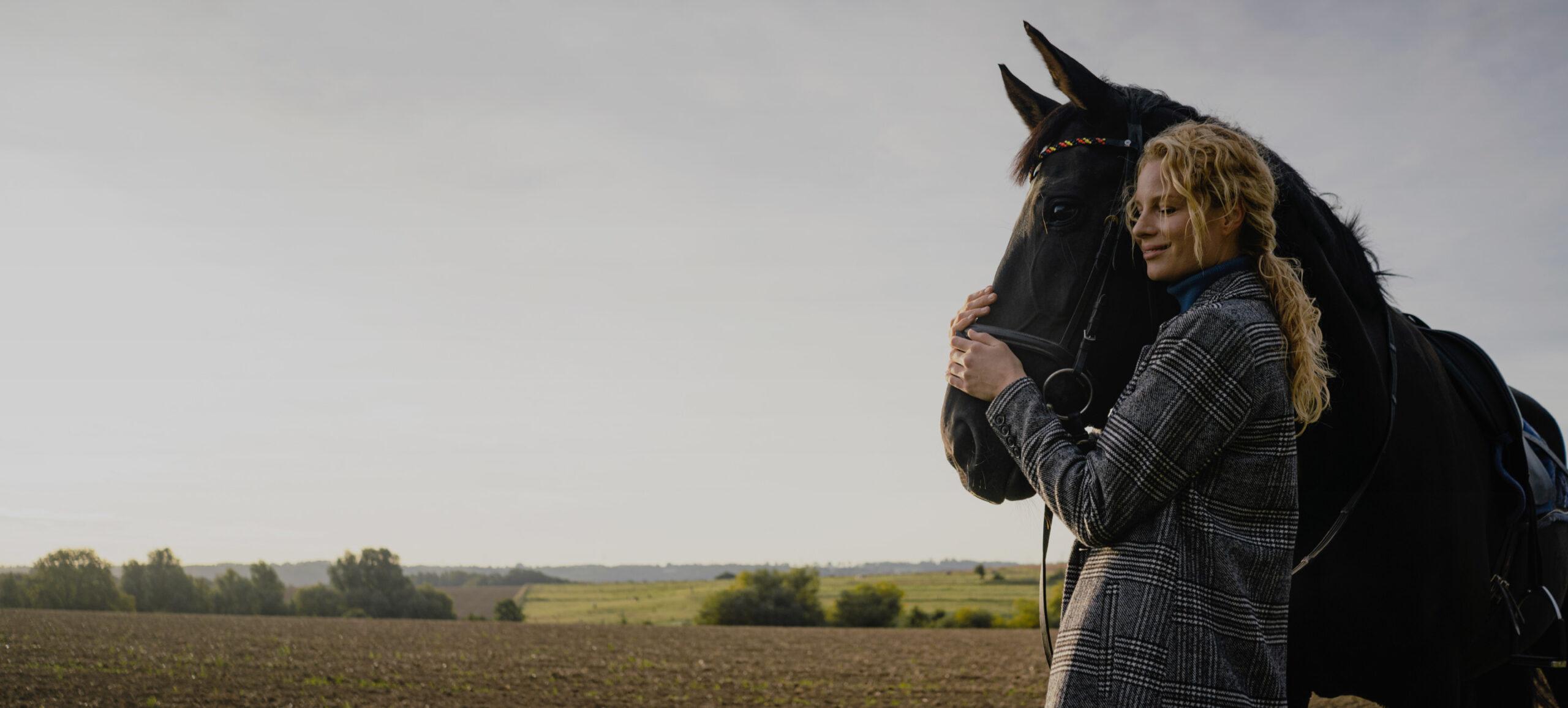 Frau steht neben Pferd und hält dessen Kopf