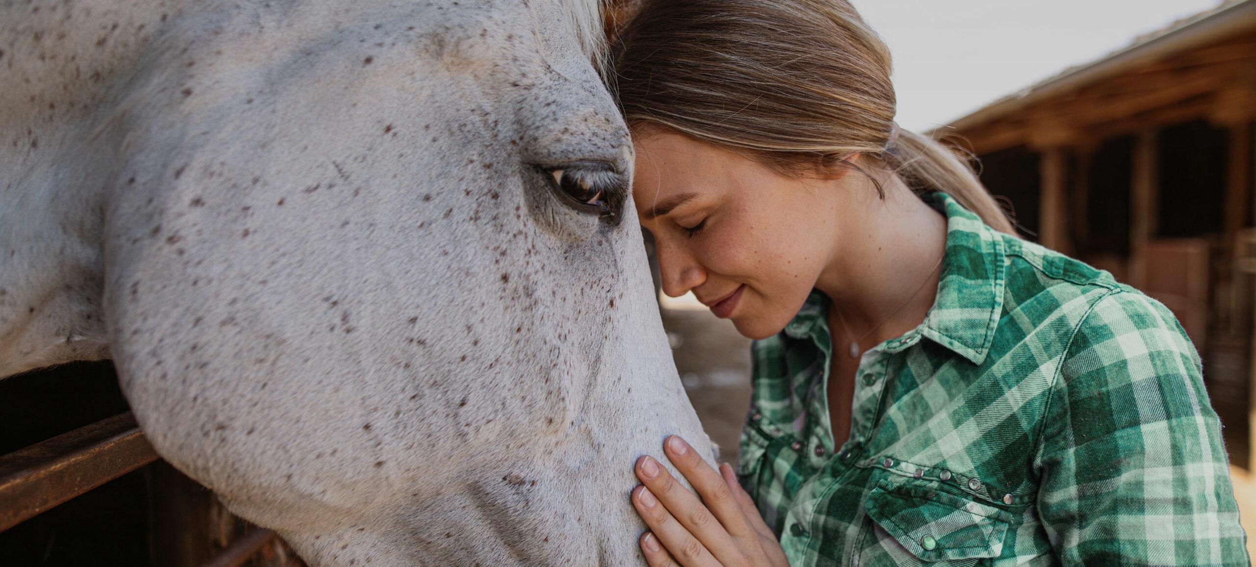 Frau lehnt mit Stirn an Pferdekopf