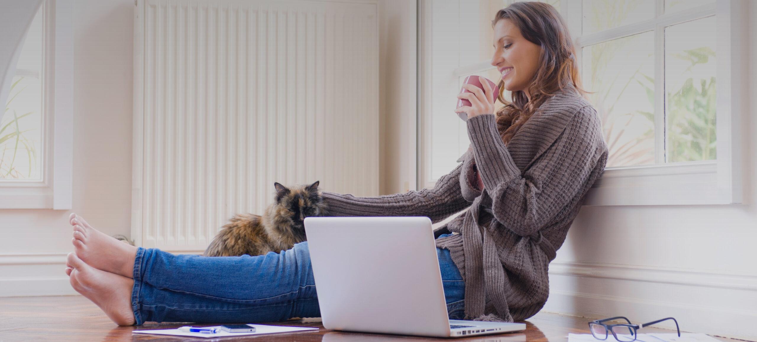 Frau sitz vor dem Laptop auf dem Boden und krault eine Katze