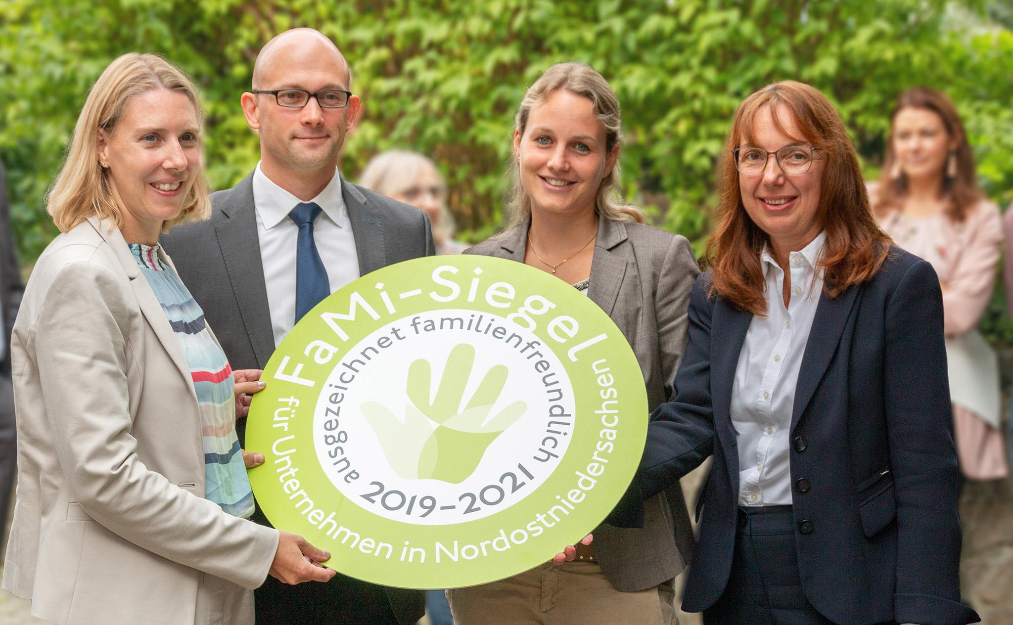Vorstand Fr. Brammer-Rahlfs und Mitarbeiter der Uelzener zeigen das FaMi-Siegel